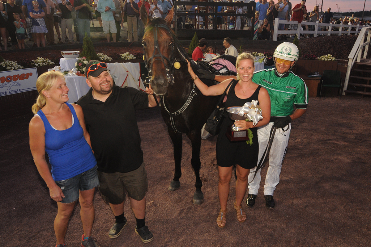 People smiling with horse at Winner's circle